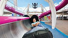 HM, Harmony of the Seas, man, father, dad, coming out at the finish, end of Ultimate Abyss slide, laughing, yelling, screaming, fun, thrills, thrilling, excited, excitement, holding on to slide mat, action, Crown & Anchor sign in background,