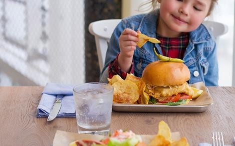 Little Girl Enjoying Fish Sandwich with Chips