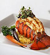 A lobster tail served with a side of rice and vegetables on a white plate at the Main Dining Room