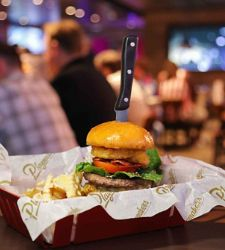 A burger with a knife stabbed in it in Playmakers Sports Bar & Arcade