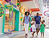 A happy family entering Sugar Beach Candy Store