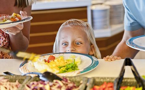 Little girl looking at fresh made scrambled eggs at the windjammer cruise buffet. Best cruise line dining experience.