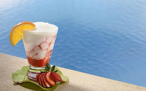 F&B, Drinks, cocktails; beverage package, 2016 Beverage shoot, Strawberry Lava Flow, mixed drink, frozen cocktail, strawberry and orange garnish, pool water in background,