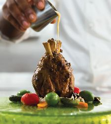 A chef pouring sauce over a beef dish on a Royal Caribbean cruise ship