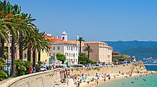 People enjoying the beach at the sea wall in Ajaccio, Corsica