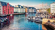Boats docked in a river in Alesund, Norway with colorful buildings on the shore