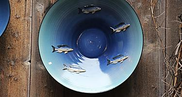 A blue traditional Norwegian bowl with fish decorations