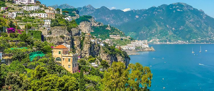 Homes lining a lush green mountain in the Amalfi Coast