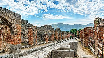 Ruins of buildings along a stone street in Pompeii, Italy