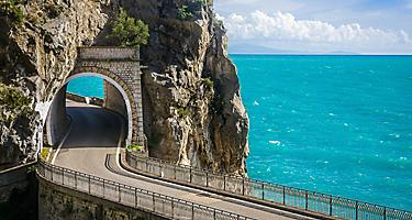 A scenic road with a tunnel through a mountain in the Amalfi Coast