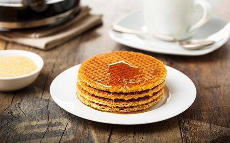 Stack of fresh Stroopwafels with honey and coffee, in a shop in Amsterdam, Netherlands