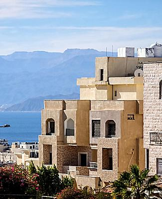 Typical Aqaba buildings on the foreground. the Gulf of Aqaba and mountains on the background