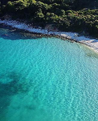 Aerial view of Kalamia beach with white rock formations and turquoise water of Argostoli, Greece