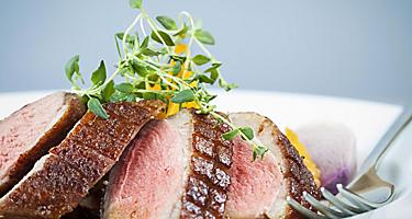 Sliced duck breast on a white plate with a fork