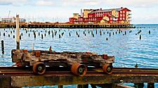 A rusted rail cart with the Cannery Pier in the distance