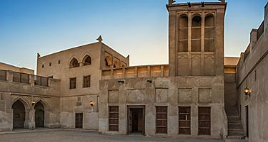 The wind-catcher tower at sunset over a courtyard of the restored traditional Arabian house of pearl trader Shaikh Isa bin Ali, in Bahrain