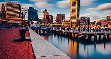 View of Inner Harbor skyline from promenade at sunset, in Baltimore