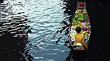 Seller on a boat with ripe bananas in the floating market of Bangkok, Thailand