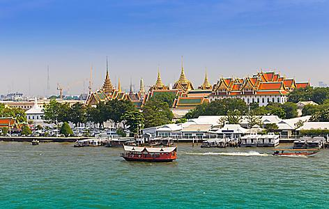 Grand palace with long tail boat in Chao Phraya River in Bangkok, Thailand