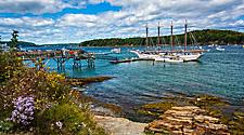 A white sailboat docked at a pier in a bay in Bar Harbor, Maine