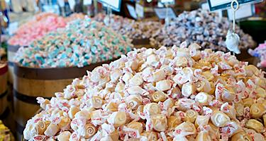 Barrels filled with various flavors of salt water taffy