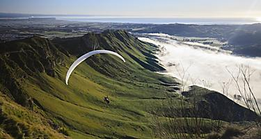 Paragliding through the mountains and bay in Bay of Islands, New Zealand