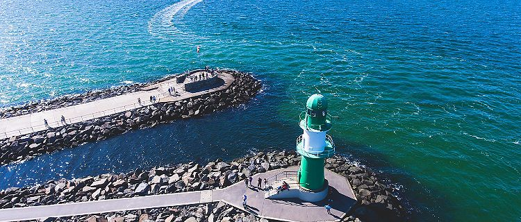 A green coastal lighthouse in Rostock, Germany