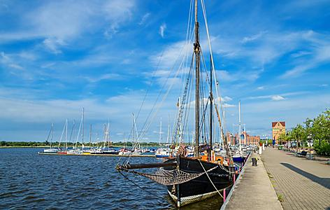 A black sailboat docked at a pier in Rostock, Germany
