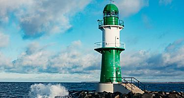 A green and white lighthouse with waves crashing against the rock jetty