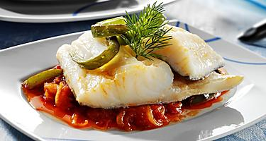 A filet of cod with side dished on a white plate
