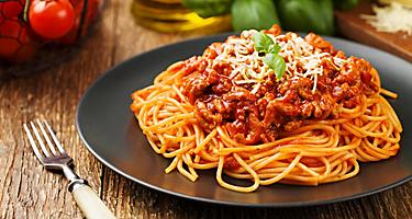 Delicious spaghetti bolognese served on a black plate in Bologna, Italy