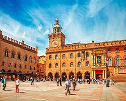 Piazza Maggiore with big clock and blue sky in Bologna, Italy