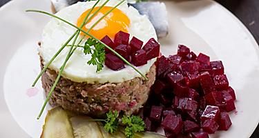 Traditional German labskaus seasoned meat, with a fried egg on top, and beetroots on the side, from a restaurant in Bremerhaven, Germany