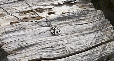 A silver necklace with a celtic symbol
