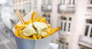 A container with fries topped with mayonnaise