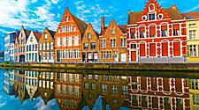 Various colorful homes reflecting on a canal in Bruges, Belgium