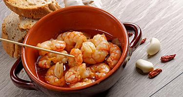 A bowl of prawns with a side of bread