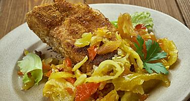 A fried filet of fish with a Creole sauce and vegetables