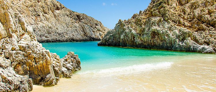 A beautiful pristine beach surrounded by rock formations in Crete