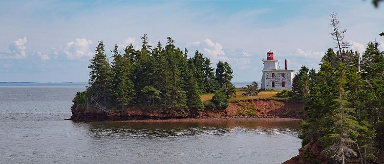A red and white lighthouse on the coast of Prince Edward Island