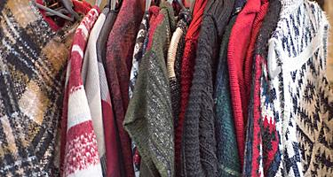 Various sweaters hanging on a rack at a shop