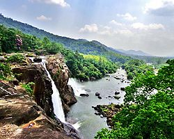 At the edge of the Athirapally Waterfall in Kerala, with a stunning view of the surrounding jungle and mountainsin Cochin, India