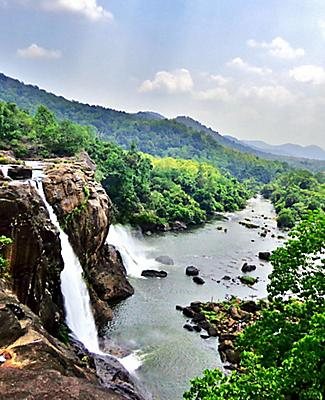 At the edge of the Athirapally Waterfall in Kerala, with a stunning view of the surrounding jungle and mountains in Cochin, India