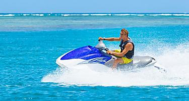 Young man riding a jetski in beautiful blue water around the private island of Coco Cay