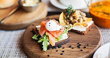 Danish smørrebrød sandwich with salmon fish and egg on wooden board, in Copenhagen, Denmark