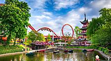 A lake with boats, with a roller coaster in the background in Tivoli Gardens in Copenhagen, Denmark