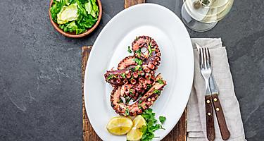 Grilled octopus served with white wine and lemons, on a restaurant in Corfu, Greece