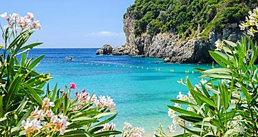 View of Palaiokastritsa Beach with beautiful flowers and blue sea water on Corfu, Greece
