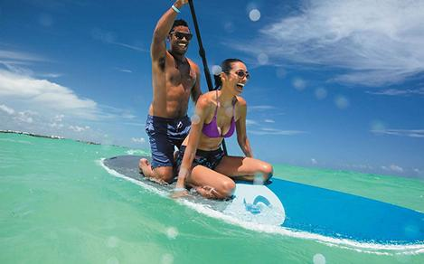 Couple having fun on a paddleboard in the water on the beach on a cruise to Cozumel, Mexico