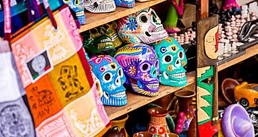 an assortment of Mexican souvenirs including painted ceramic skulls